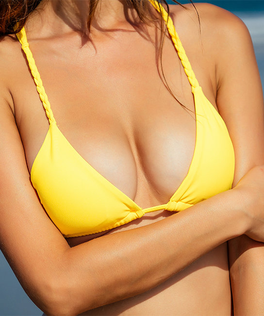 prominent breasts in yellow bikini top