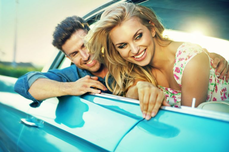 smiling couple in classic car